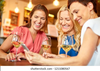 people, technology and lifestyle concept - women with smartphone drinking wine at bar or restaurant