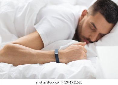 people, technology and rest concept - close up of man with activity tracker sleeping in bed