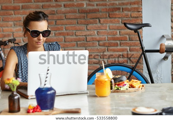 People and technology. Serious and confident businesswoman dressed casually using laptop pc for remote work, sitting at cozy cafeteria with brick wall, checking her email during lunch on weekend