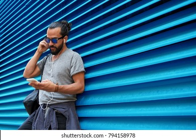 people, technology, travel and tourism - man with earphones, smartphone and bag on city street and listening to music over ribbed blue wall background