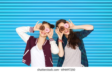 people, teens and fast food concept - happy smiling pretty teenage girls or friends with donuts making faces and having fun over blue ribbed background