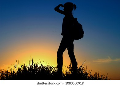People, Teens, Hiking and Travel Concept. Silhouette Of A Young Girl On A Mountain Top.Young Girl With Backpack Enjoying Sunset.Tourist Traveler At Sunset.
