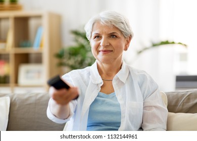 people, television and entertainment concept - senior woman in eyeglasses with remote control watching tv at home