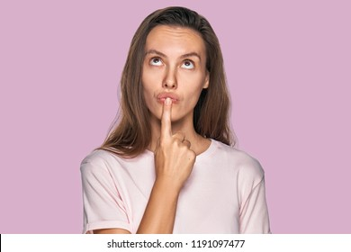 People and thoughts concept. Attractive Caucasian woman looks pensive upwards, keeps forefinger near lips, plans day, has something in mind on lavender studio. Clever woman thinks about new project.