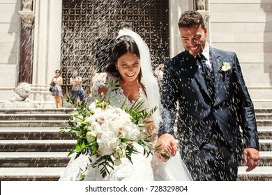 People throw rice on newlyweds walking out of the church