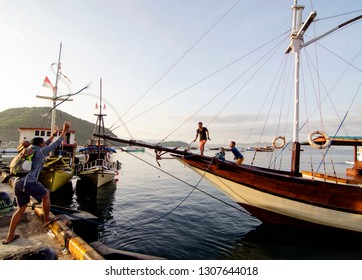 People throwing tail at phinisi boat in Labuan Bajo Port, Komodo Island, Indonesia. On Saturday January 7, 2017.