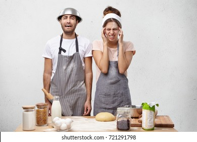 People, tiredness and overwork concept. Fatigue cookes have headache, work hard all day, have stressful expressions, going to cry as find out they should bake one more pastry, haven`t any desire