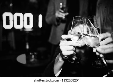 People toasting with a glass of champagne in a NYE party