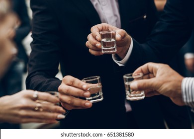 people toasting holding glasses of vodka cheering at wedding reception, celebration outdoors, catering in restaurant. christmas and new year