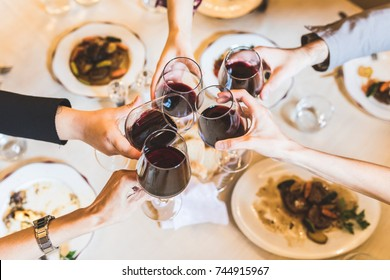 People toasting with red wine at restaurant. Close up view of five hands holding glasses with wine, and some food on the table. Lifestyle and drinks concept with an Italian style.