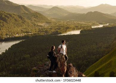 people at the top of the mountain overlooking the valley and the river at sunset
