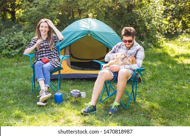 People, tourism and nature concept - Couple having fun on camping trip