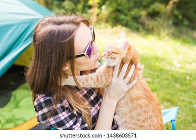 People, tourism and nature concept - Woman in sunglasses holding a cat sitting near the tent