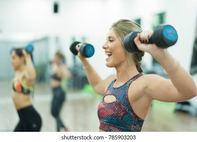 People training body pump exercises, blonde woman laughs