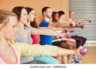 People training with weights in fitness class at the gym