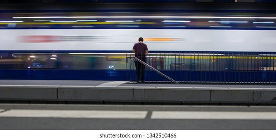 People in a trainstation with motion blurred trains moving fast (color toned image)