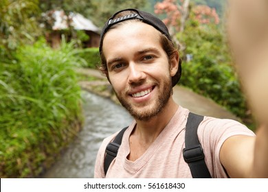 People, travel and adventure concept. Attractive young bearded adventurer wearing backpack and cap taking selfie, standing in the middle of country road with greenery and river running in background