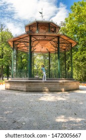 People, travel and summer holidays concept. Young woman posing in the beautiful green garden pavilion. Mestsky or City park of Kosice, Slovakia (Slovensko), vertical image - Shutterstock ID 1472005667