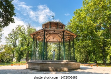 People, travel and summer holidays concept. Young woman posing in the beautiful green garden pavilion. Mestsky or City park of Kosice, Slovakia (Slovensko) - Shutterstock ID 1472005688
