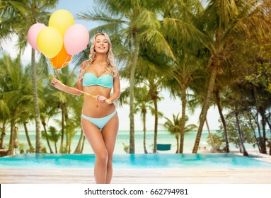 people, travel and summer holidays concept - happy smiling young woman in bikini swimsuit holding air balloons over exotic tropical beach with palm trees and outdoor pool background