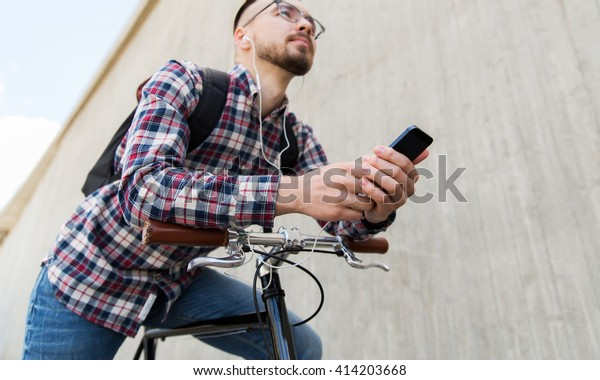 people, travel, technology, leisure and lifestyle - close up of young hipster man in earphones with smartphone and fixed gear bike listening to music on city street