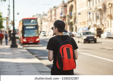 People, travel, tourism and education concept - stylish young man with backpack over london city bus on street background.