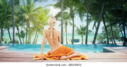 people, travel, tourism, summer and people concept - woman with orange towel from back over tropical beach with swimming pool background