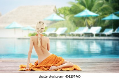 people, travel, tourism, summer vacation and people concept - woman with orange towel from back over exotic hotel resort beach with swimming pool and sunbeds background