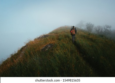 """People or traveler walk on the Mountain hill with grass field with sea of fog or white clouds at """"Doi MonJong"""" Chiangmai, Thailand, Asia."""