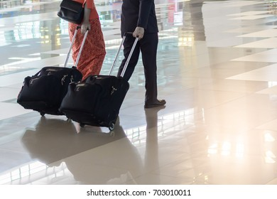 people and traveling luggage walking in airport terminal building