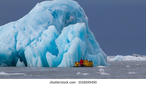 people traveling in a zodiac in beween icebergs of Svalbard