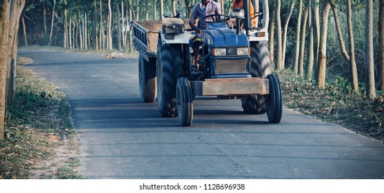 People travelling on a traditional tractor vehicles in the road unique photo