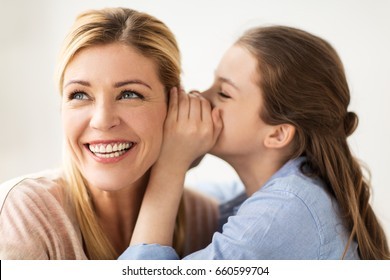 people, trust and family concept - happy daughter whispering secret to her mother