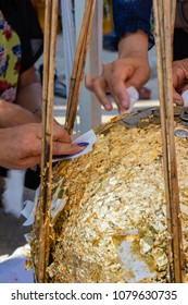 People try to stick a gold leave on buried stone when thai tradi