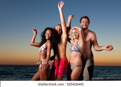 People (two couples) on the beach having a party, having a lot of fun in the sunset