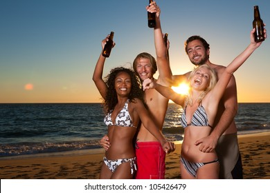 People (two couples) on the beach having a party, drinking and having a lot of fun in the sunset (people having bottles in their hands)
