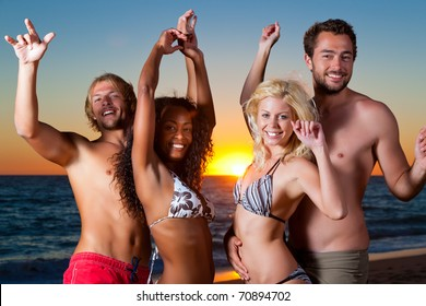 People (two couples) on the beach having a party, dancing and having a lot of fun in the sunset