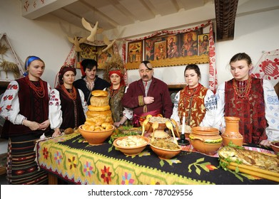People in Ukrainian native dresses standing behind table with traditional dishes to celebrate Christmas Eve. Reconstruction of Ukrainian folk traditions for mass-media. January 4, 2018. Kiev, Ukraine