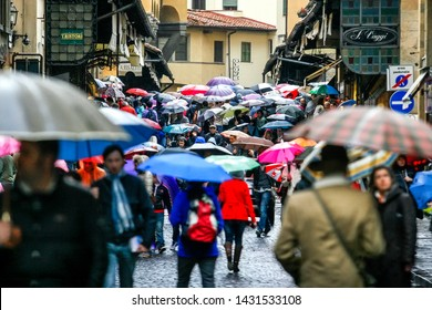People with umbrellas walk along Old bridge Ponte Vecchio over the river Arno in Florance, Tuscany, Italy. Rainy day, April 2012