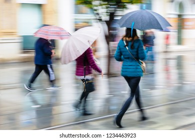people with umbrellas walking in the city on a rainy day, picture made with motion blur effect