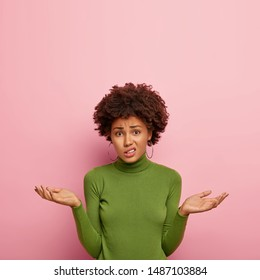 People and uncertainty concept. Displeased hesitant female model spreads palms with doubt, looks confusingly at camera, wears green sweater, poses against pink background, copy space upwards
