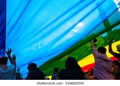 People under the 8 color gay pride flag used at 2017's Sao Paulo LGBT Pride Parade. This flag is a reproduction of the original 1978 design and also a tribute to its creator Gilbert Baker.