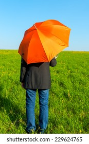 people under an orange umbrella in a field waiting for rain
