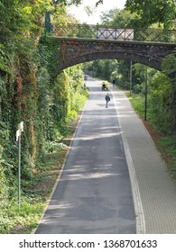 People under way on the Nordbahntrasse, a former railway line in Wuppertal in autumn 2017. The rock walls are covered with climbing plants.The popular track has been rebuilt into a leisure walk.