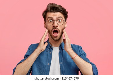 People and unexpectedness concept. Shocked young male with stubble, opens mouth widely, keeps hands on cheeks, notices something unbelievable, wears round spectacles and denim shirt, stands indoor