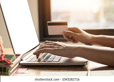 people use notebook and holding credit card for shopping online on office desk