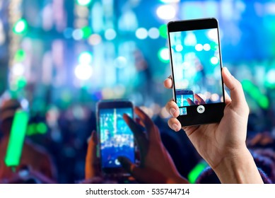 people use smart phones record video at music concert