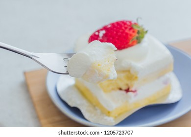 People are using hand fork strawberry cake tastes delicious on blue plate in the shop a bekery , soft focus , blurred.