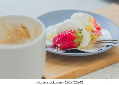 People are using hand fork strawberry cake tastes delicious on blue plate Served with hot cup of cappuccino white in a bekery , soft focus , blurred.