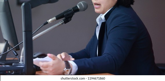 The people is using the microphone to perform the public speaking.